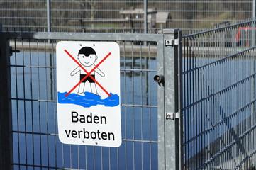 """Zeichen: """"Baden verboten"""" an einem verzinkten Eisengitterzaun um einen Löschwasserspeicher"""