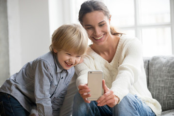 Happy mother laughing taking selfie with little son on smartphone at home, smiling single mom and cute adopted boy playing making photo posing for self portrait, mommy and kid watching video on cell
