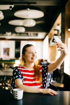 Happy young woman taking selfie on smartphone wearing short with colors of american flag