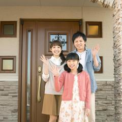 玄関の前で手を振る親子