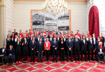 French President Emmanuel Macron (C) poses for a family picture with French members of the International Olympic Committee and French athletes in Paris