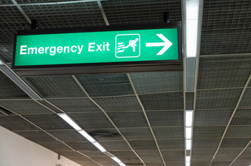 green emergency fire exit sign on ceiling in office building, subway train station, airport or shopping mall