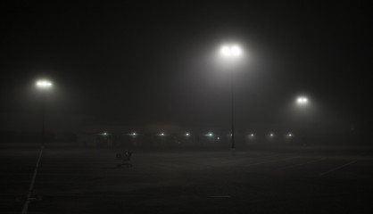 Empty parking lot in a foggy night with lanterns