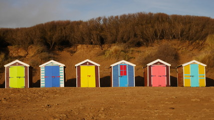 Colourful beach huts and blue sky at Saunton Sands, Devon, England