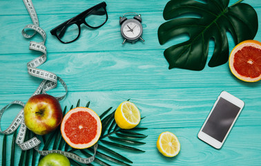 Creative layout made of summer tropical fruits and leaves. Flat lay. Fitness concept.