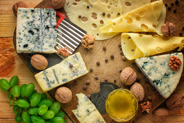 Cheese platter with different cheeses, grapes, nuts, honey and dates on rustic wooden background. Retro styled cheese variety selection on wood board.
