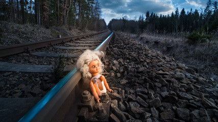 Train track with old doll lit by mystery light. Broken abandoned child toy at the rusty rail in dark forest. Idea of fate, apocalypse, sci-fi, war or abuse.