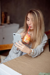 Happy woman sipping fresh summer lemonade while. Caucasian young girl 20-25 years old sits at the table indoor looking at her smartphone.