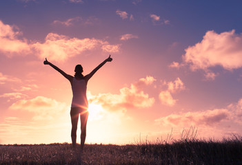 Young woman raising her arms up against the sunset feeling free. Happiness and joy concept.