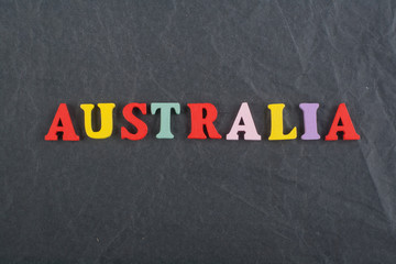 AUSTRALIA word on black board background composed from colorful abc alphabet block wooden letters, copy space for ad text. Learning english concept.