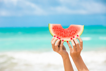 Hand holding slice of watermelon on tropical beach. Summer sun kiss colors.