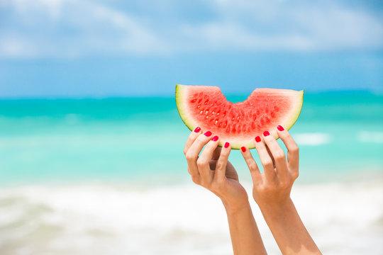Hand holding slice of watermelon on tropical beach. Summer sun kiss colors.