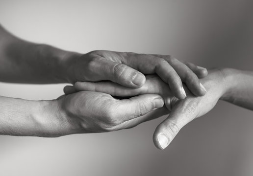Hand holding another hand. People helping and comforting each other concept.
