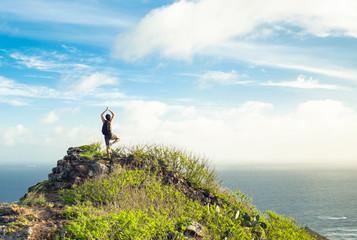Man doing yoga on a mountain.