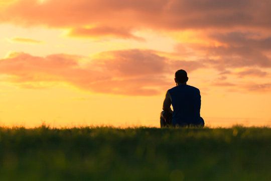 Man sitting alone watching the beautiful sunset.