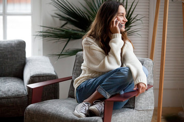 Happy cheerful young woman talking on the phone at home, smiling teen girl making answering call by cellphone sitting on chair, beautiful lady having pleasant funny conversation speaking by mobile