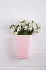 Spring bouquet of snowdrops in paper box on white wooden background
