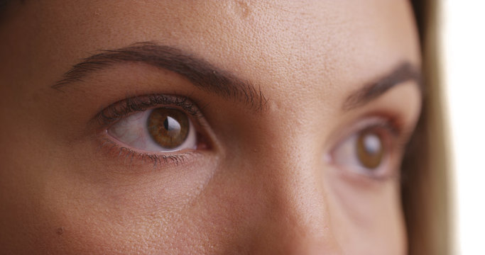 Close up of female millennial's eyes blinking on white background