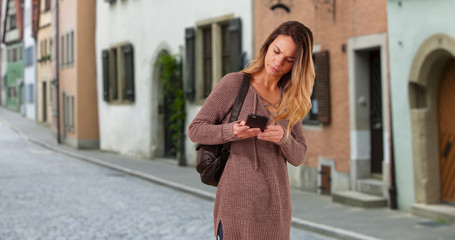Caucasian woman wandering down village street outside apartments in Europe