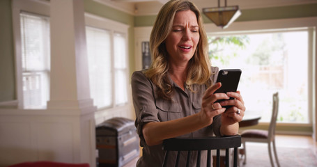 Caucasian woman looking at pictures on smartphone in room seated in chair