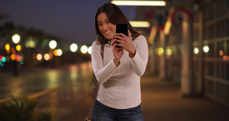Portrait of Latina woman taking photo of someone with phone and giving thumbs up