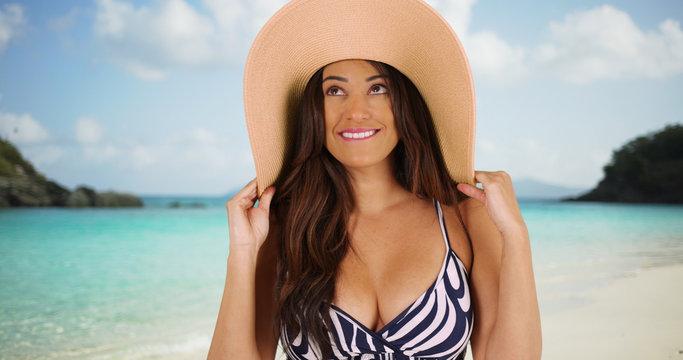 Latina female playfully modeling floppy sunhat by the ocean on Caribbean beach