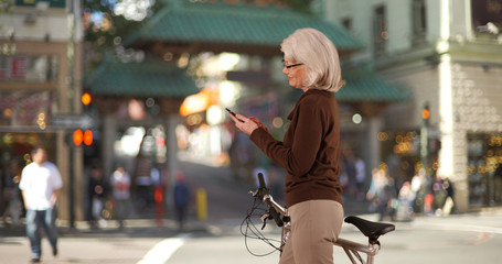 Mature Caucasian woman standing with bike using smartphone in Chinatown San Francisco