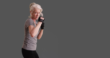 Athletic woman in her 50s posed in martial arts stance on gray backdrop