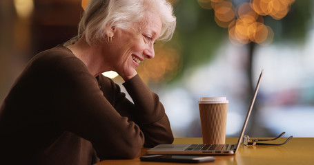 Profile of cheerful Caucasian woman in her 50s video chatting with someone on laptop outside