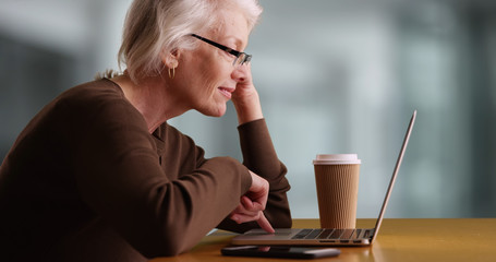 Modern female elder browsing internet and drinking coffee inside office building
