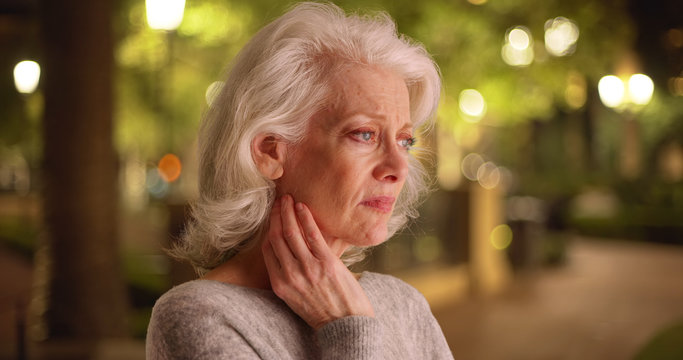 Close view of mature white woman with unhappy look on face outside at night