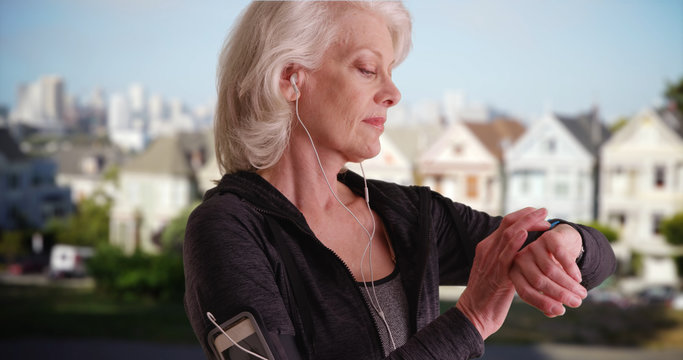 Athletic senior woman out jogging in San Francisco looking at watch outside