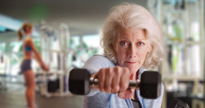 Fit elderly white lady at gym working out and looking at camera with determination