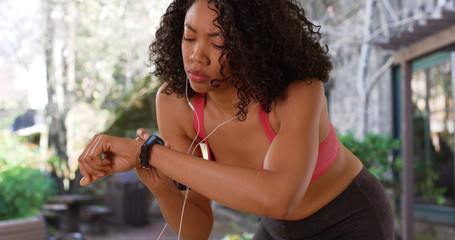 African-American woman runner in sports bra checking pulse rate on watch outside