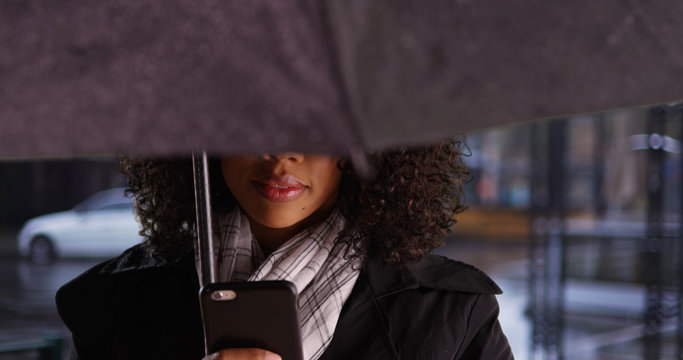 Mysterious African woman with umbrella checking mobile device in the rain