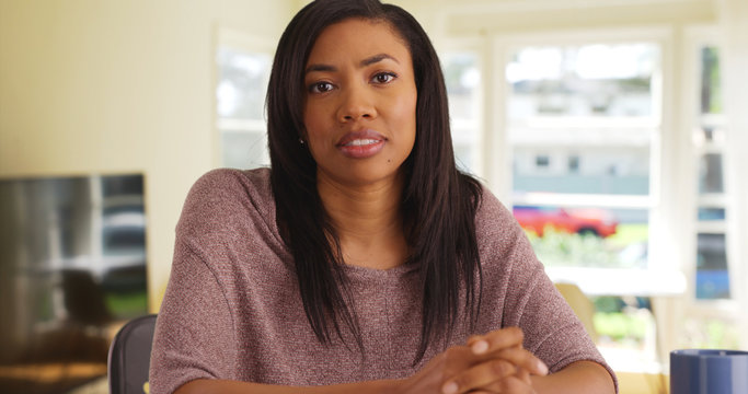 Modern African female sitting in living room with concerned expression on face