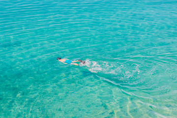 Aerial view of young man snorkeling in the transparent turquoise sea. Top view of man relaxing on her holidays.