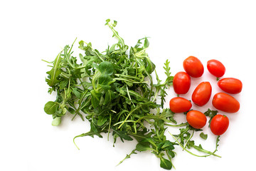 Green arugula salad and red tomatoes on white background