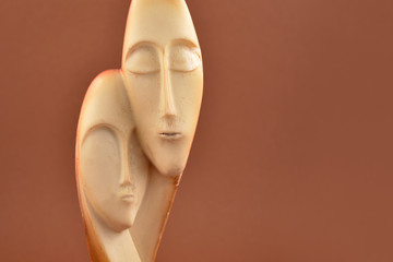 Love faces stock images. Loving couple decoration. Couple statue isolated on a brown background. Man and woman statue. Face of man and woman