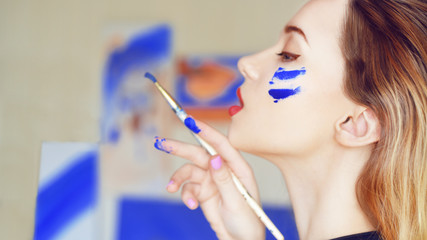 Young artist painting. Girl painting a picture in home studio. Model painting brush on easel. Sensual woman with paint on the face. Girl holding a paintbrush with blue paint. Girl with a hobby.