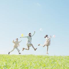 風船を持ち草原でジャンプをする3人の女性