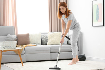 Housewife hoovering carpet at home