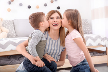 Cute little children kissing their nanny at home