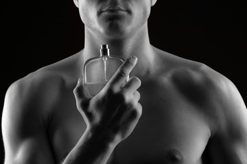 Handsome man using perfume on black background, closeup. Black and white effect