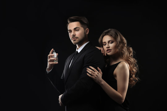 Passionate woman and handsome man using perfume on black background