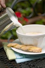 latte mug with foam pouring on top and twisted cookie