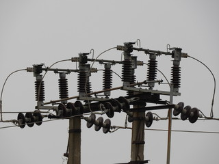 Electrical concrete pole with primary wires, insulators, transformers against sky