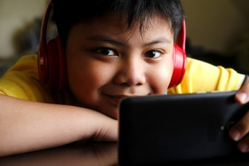 Young Asian boy with a smartphone and headphones