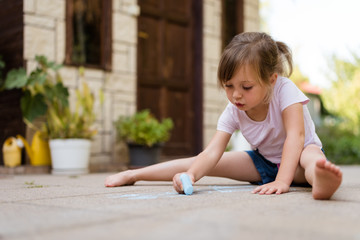Creativity - girl drawing with chalk outdoors