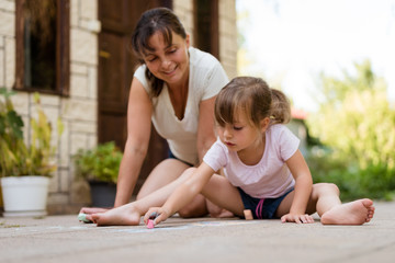 Playing together - mother with child drawing with chalk